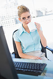 Relaxed businesswoman wearing glasses drinking coffee