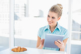 Cheerful classy woman using tablet while having breakfast