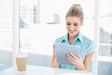 Smiling classy woman using tablet while having a break