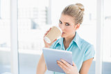 Relaxed classy woman using tablet while drinking coffee