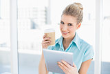 Smiling classy woman using tablet holding coffee