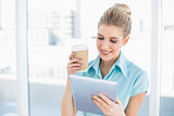 Cheerful classy woman using tablet holding coffee