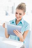 Cheerful elegant woman using tablet holding coffee