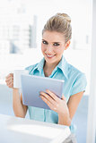 Smiling elegant woman using tablet holding coffee