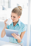Relaxed elegant woman using tablet while drinking coffee