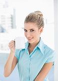 Smiling elegant woman holding coffee