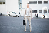 Serious stylish businesswoman holding briefcase posing