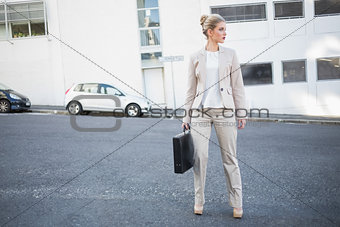 Serious classy businesswoman holding briefcase posing