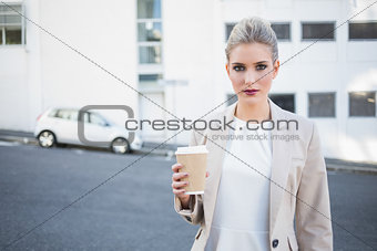 Serious stylish businesswoman holding coffee