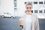 Cheerful stylish businesswoman holding coffee