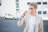 Cheerful stylish businesswoman drinking coffee