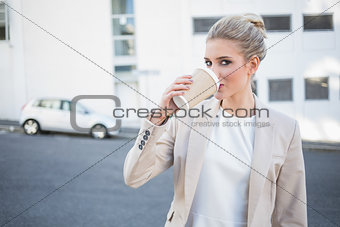 Cheerful stylish businesswoman drinking coffee