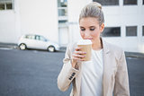 Peaceful stylish businesswoman smelling coffee