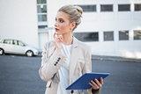 Thoughtful stylish businesswoman using digital tablet