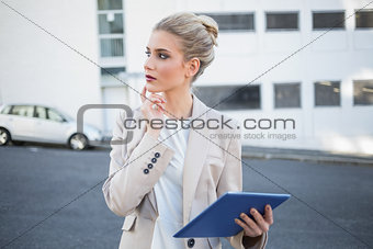 Thoughtful stylish businesswoman using digital tablet