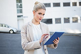 Relaxed stylish businesswoman scrolling on digital tablet
