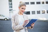 Cheerful stylish businesswoman scrolling on digital tablet