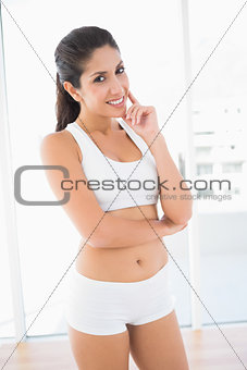 Fit confident woman in sportswear smiling at camera
