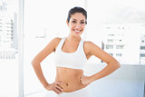 Fit happy woman in sportswear with hands on hips