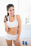 Fit laughing woman in sportswear holding jump rope