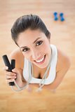 Fit happy woman holding jump rope