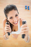Fit smiling woman holding jump rope