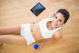 Fit smiling woman holding sports bottle lying on wooden floor