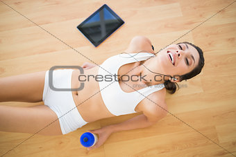 Fit smiling woman holding sports bottle resting