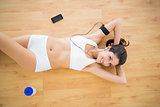 Fit happy woman doing sit ups listening to music
