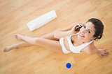 Fit happy woman taking a call during her workout looking at camera