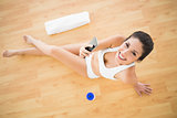 Fit happy woman sending a text during her workout looking at camera