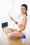 Fit woman sending a text smiling at camera
