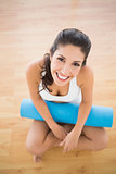 Fit woman holding her exercise mat sitting and smiling at camera