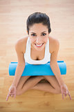 Pretty woman with her exercise mat sitting in lotus pose