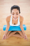 Calm woman with her exercise mat sitting in lotus pose
