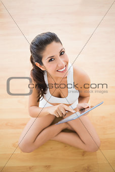 Fit woman sitting and using her tablet pc smiling at camera