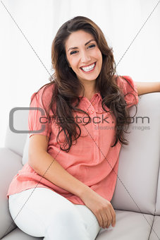 Beautiful brunette sitting on her couch smiling at camera