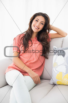Smiling brunette sitting on her couch looking at camera