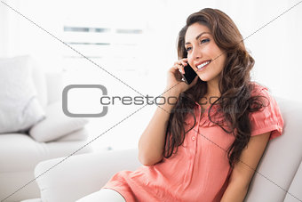 Smiling brunette sitting on her couch on a phone call