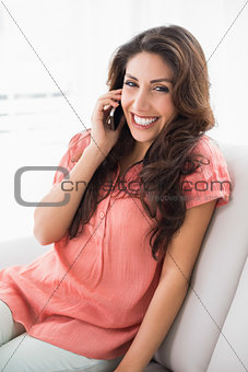 Pretty brunette sitting on her couch on a phone call