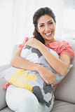 Laughing brunette sitting on her sofa smiling at camera