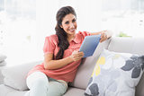 Smiling brunette sitting on her sofa using tablet