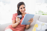 Smiling brunette sitting on her sofa using tablet to shop online