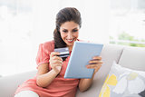 Happy brunette sitting on her sofa using tablet to shop online