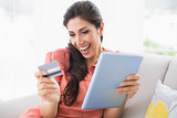 Excited brunette sitting on her sofa using tablet to shop online