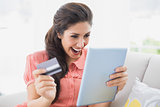 Ecstatic brunette sitting on her sofa using tablet to shop online