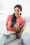 Excited brunette sitting on her sofa using laptop to shop online