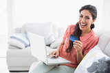 Laughing brunette sitting on her sofa using laptop to shop online