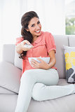 Cheerful brunette sitting on her sofa watching tv holding bowl of popcorn