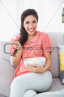 Cheerful brunette sitting on her sofa eating bowl of popcorn